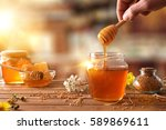 hand with dipper picking honey... | Shutterstock . vector #589869611