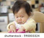 baby eating messy mashed potato | Shutterstock . vector #590003324
