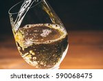 pouring white wine from a... | Shutterstock . vector #590068475