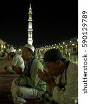 Small photo of Madinah, Saudi Arabia - November 3, 2009; Muslims make a 'doa' and a view of 'Masjidil Nabawi' or prophet's mosque tower in Madinah.