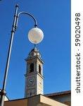 Yellow church clock tower against blue sky, Locate Di Triulzi, Milan, Lombardy, Italy - stock photo