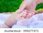 mother holding baby hand   Shutterstock . vector #590277371