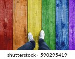 Small photo of Top view of a single man standing on rainbow gay pride colored wooden floor. Personal perspective used.