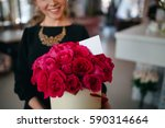 Stock photo girl in black blouse holds gift in hands of rich bouquet of red roses composition of flowers in 590314664