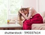 young woman sitting on a living ... | Shutterstock . vector #590337614