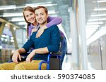 Small photo of Portrait of young happy couple: pretty girl hugging her smiling handicapped boyfriend in wheelchair