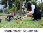 the girl is feeding to a group... | Shutterstock . vector #590385587