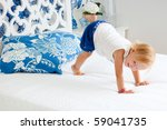 Portrait of adorable playful toddler girl jumping on bed in nicely decorated bedroom - stock photo