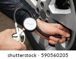 Small photo of Auto mechanic checking tire pressure, closeup