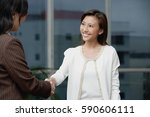 businesswomen shaking hands | Shutterstock . vector #590606111