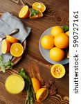 Small photo of Rustic wooden kitchen table with fruits and spices laid out on it, all set for squeezing fresh juice: delicious ripe oranges cut in half, mint and star anise scattered in elegant assortment