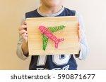 Child Holding String Art Plane