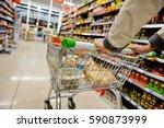 a shopper pushes a trolley... | Shutterstock . vector #590873999