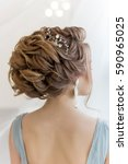 Small photo of beautiful volume hairstyle for a bride in a gentle blue light dress with large earrings and adornment in hair