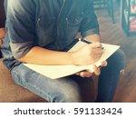 man writing journal on the book ...   Shutterstock . vector #591133424