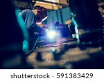 welding steel with sparks using ... | Shutterstock . vector #591383429