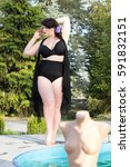 Small photo of Young beautiful busty curvy plus size model with big breast in black bra, professional makeup and hairstyle near the outdoors pool