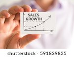 Small photo of Closeup on businessman holding a card with SALES GROWTH rising arrow and chart, business concept image with soft focus background