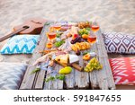 picnic on the beach at sunset... | Shutterstock . vector #591847655