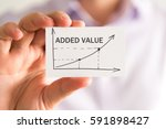 Small photo of Closeup on businessman holding a card with ADDED VALUE rising arrow and chart, business concept image with soft focus background