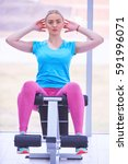 Small photo of Attractive fit woman working out abs in fitness gym, making ab intervals
