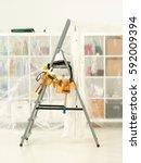 tools belt and overalls hanging ... | Shutterstock . vector #592009394