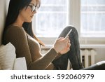 a young girl using a smartphone ... | Shutterstock . vector #592060979