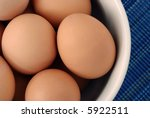 Close-up of fresh, brown eggs in a ceramic bowl with blue background. Shallow dof - stock photo