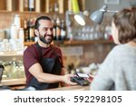 Small photo of small business, people and service concept - happy man or waiter in apron with card reader and customer with smartphone paying at bar of coffee shop
