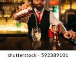 bartender is making alcohol... | Shutterstock . vector #592389101
