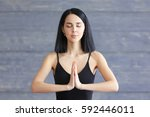 Small photo of Portrait of beautiful smiling brunette young woman enjoying yoga. Yoga girl relax, breath and meditating with closed eyes on wooden background on studio, copy space