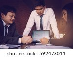 three business people serious... | Shutterstock . vector #592473011