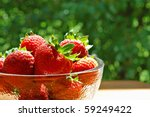 Sunlit bowl of fresh strawberries on outside table with summer foliage in background.  Macro with shallow dof. - stock photo