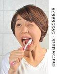 asian woman brushing her teeth | Shutterstock . vector #592586879