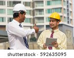 two men wearing hard hats and... | Shutterstock . vector #592635095