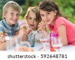 three children having a snack... | Shutterstock . vector #592648781