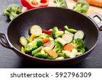 stir fried vegetables in a wok... | Shutterstock . vector #592796309