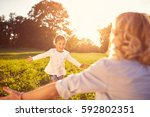 nice little girl run to mother... | Shutterstock . vector #592802351