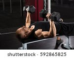 man lying on bench press while... | Shutterstock . vector #592865825