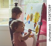 Small photo of Two little girls painting on the easel, selective focus, toned