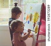 two little girls painting on... | Shutterstock . vector #592873289