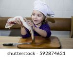 girl  to clean a live fish  joy ... | Shutterstock . vector #592874621
