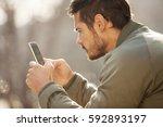 handsome modern man using smart ... | Shutterstock . vector #592893197