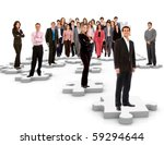 Group of business people standing on the pieces of a puzzle - isolated over a white background - stock photo