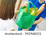 delivery man giving grocery bag ... | Shutterstock . vector #592968221