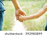 the parent holding the child's...   Shutterstock . vector #592983899