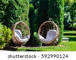 Two Hanging Chairs In A Garden...