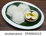 Small photo of Noolappam/Idiyappam/rice noodles, a popular traditional steam cooked Kerala breakfast dish with hot and spicy egg roast curry on a houseboat, Alleppey, India. South Indian food. noolputtu Sri lankan