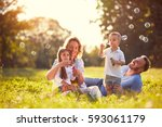 family with children blow soap... | Shutterstock . vector #593061179