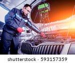 auto mechanic uses a voltmeter...   Shutterstock . vector #593157359